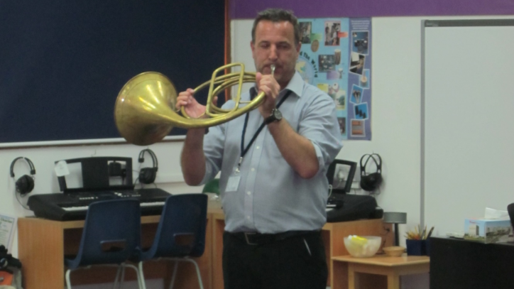 Daniel playing the french horn in a classroom