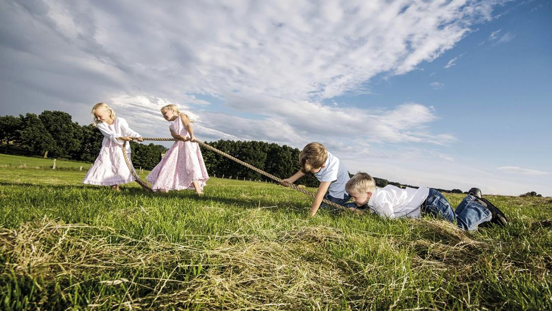 Two girls beating two boys at tug of war on a grassy hill - gender gap reading