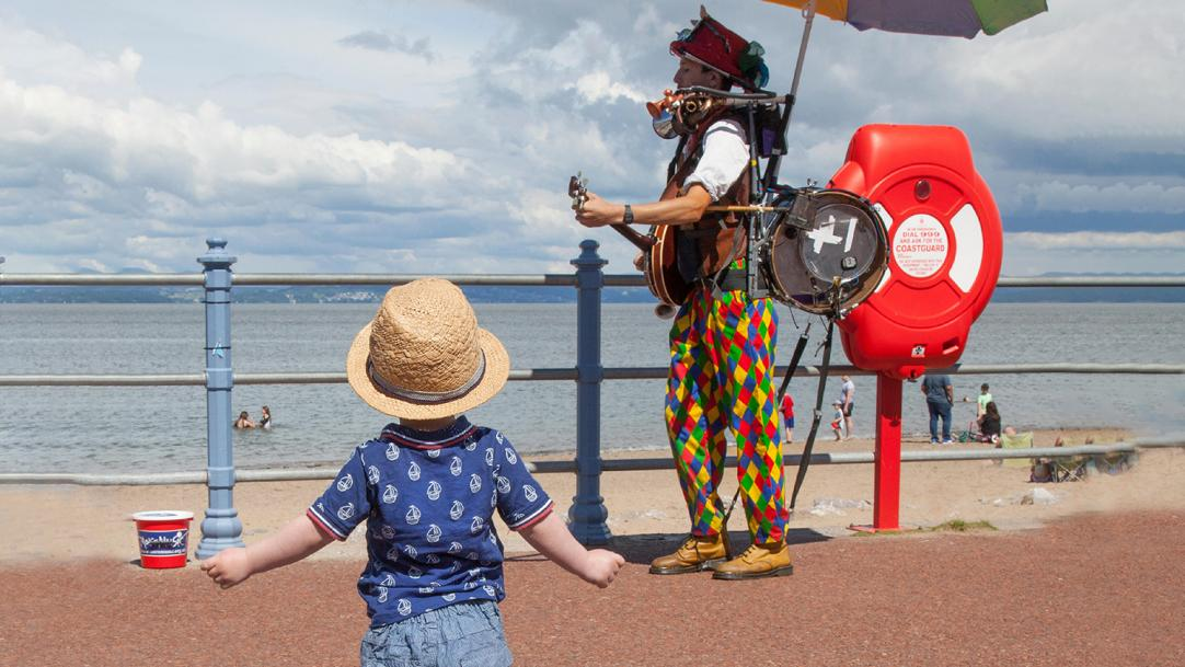 Solo baby approaches one-man band on a seafront promenade - independent learners
