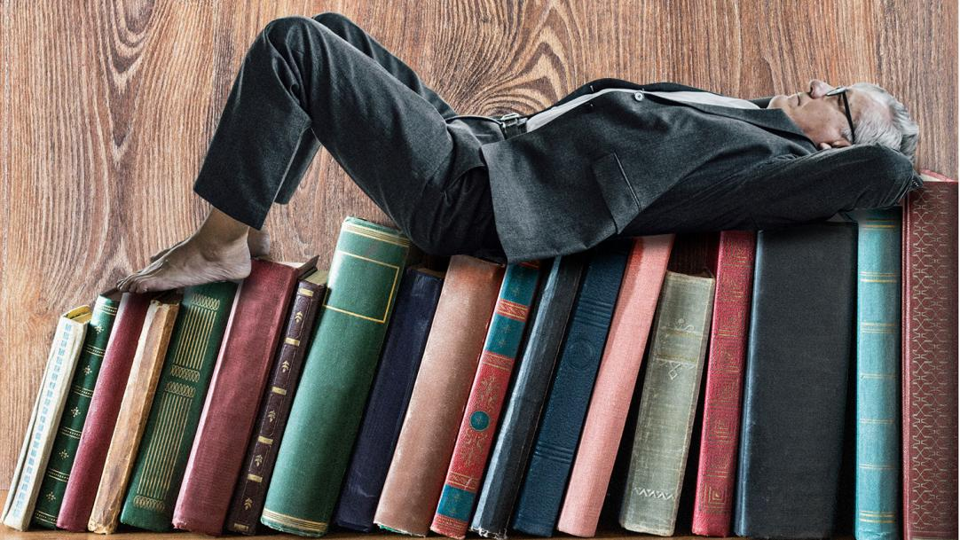 A man lying on a shelf of books – reading relaxation teachers