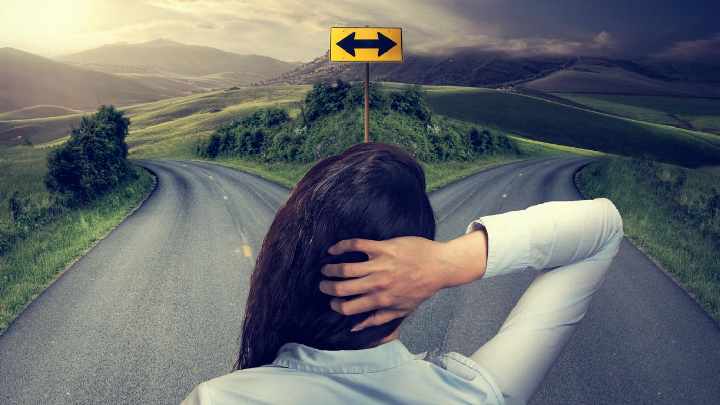 A woman, standing staring at a fork in the road
