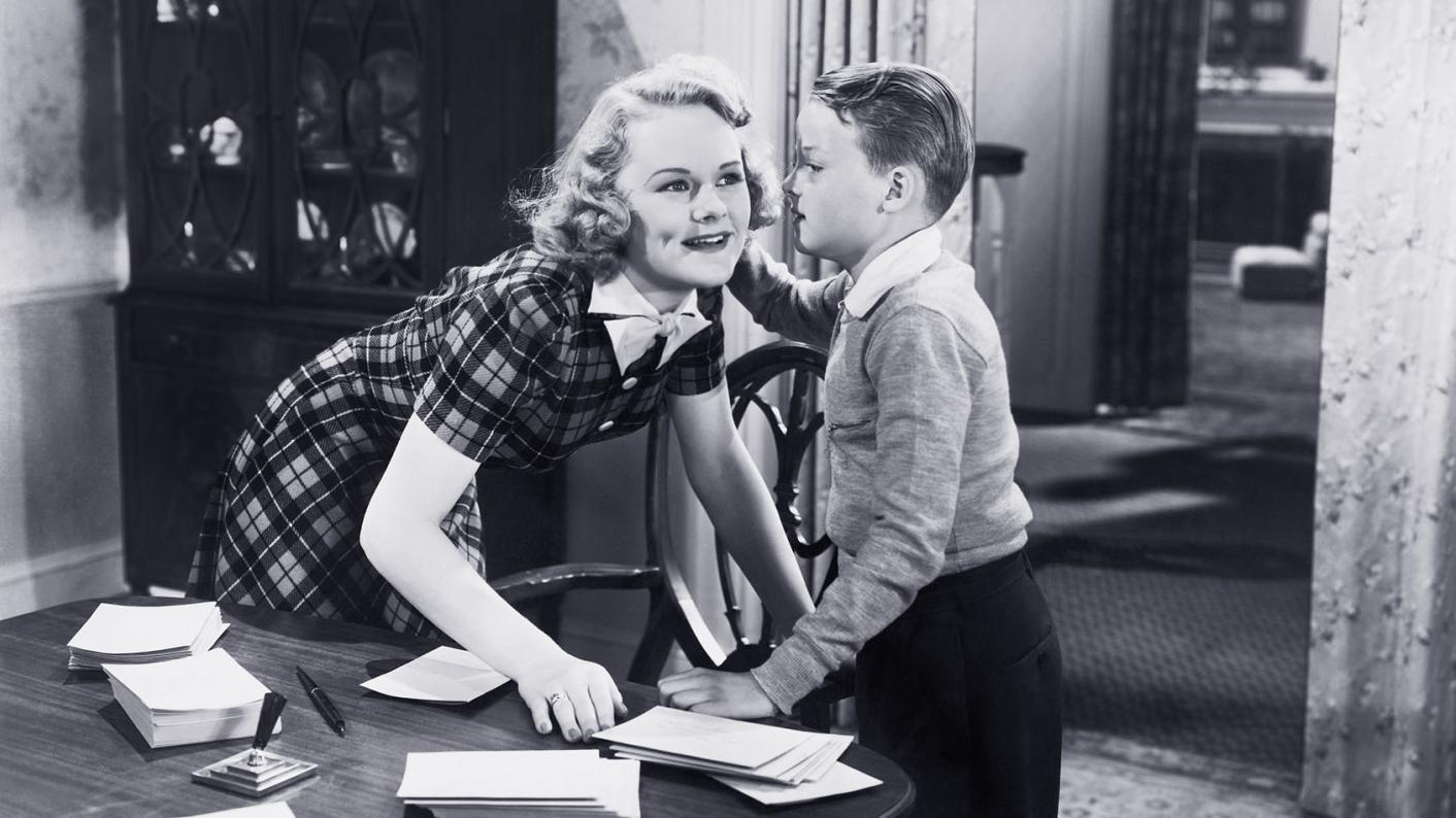 Old still of child saying something in teacher's ear