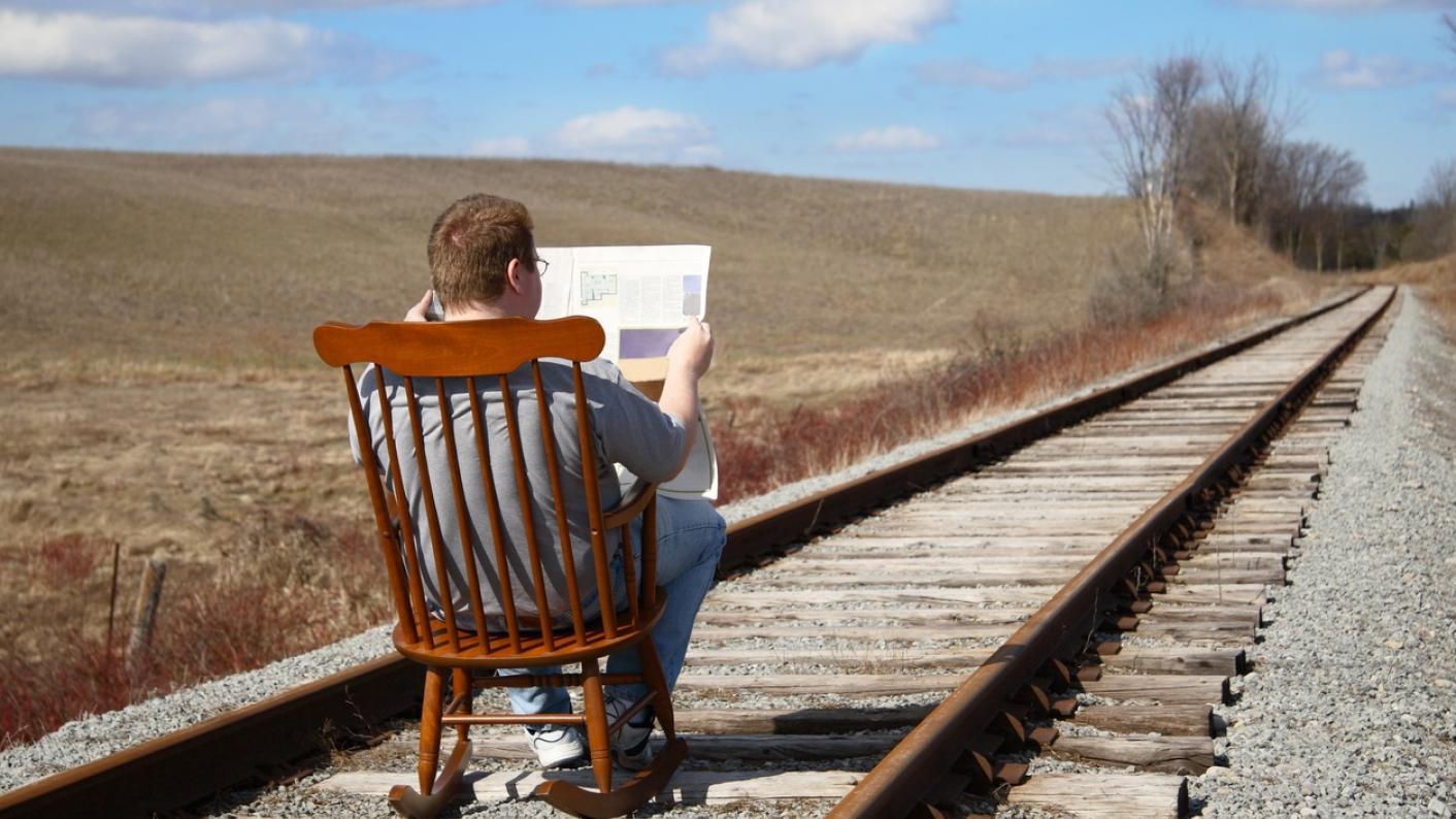 Man reading on train tracks