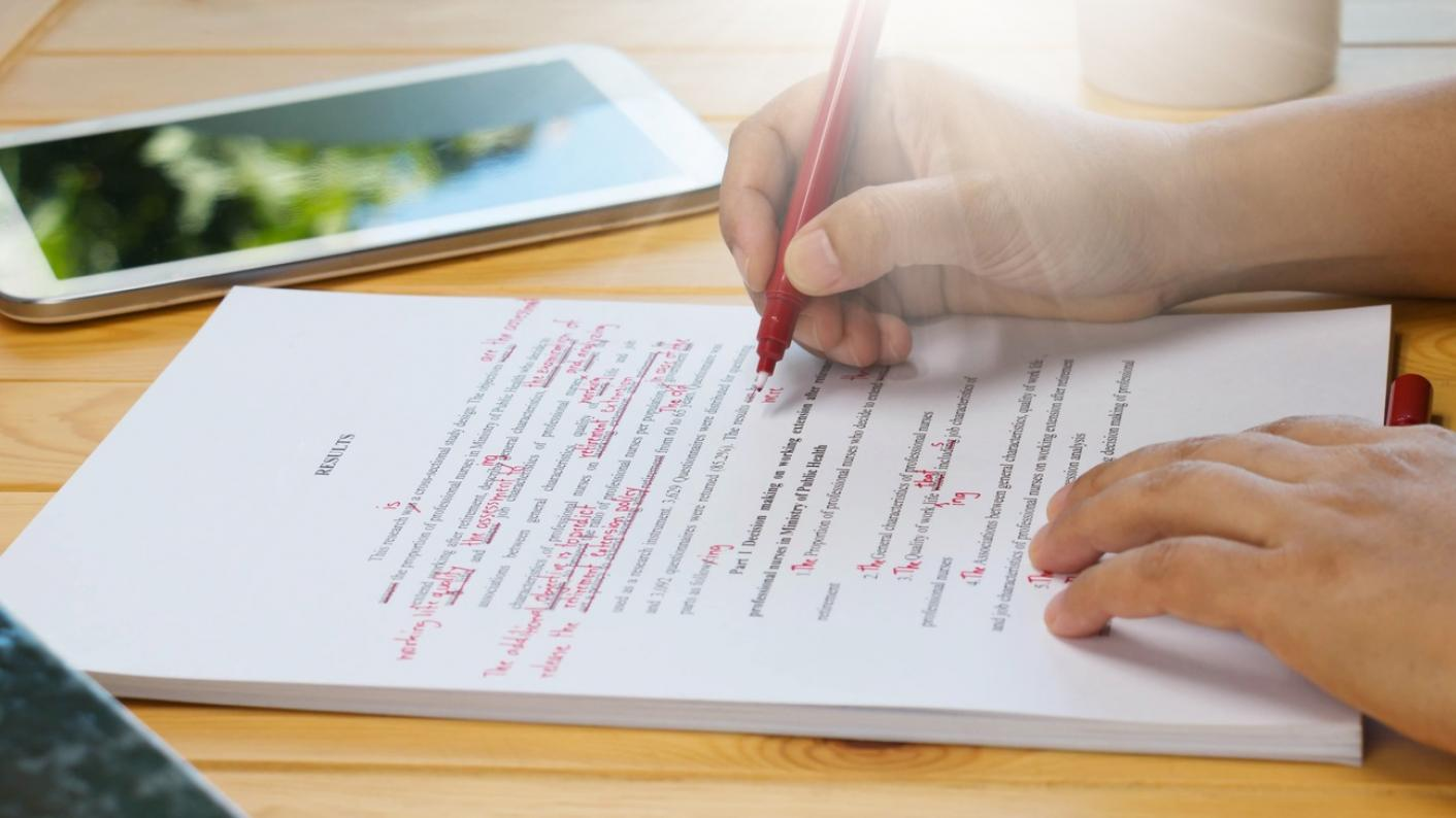 Person correcting essay with red ink