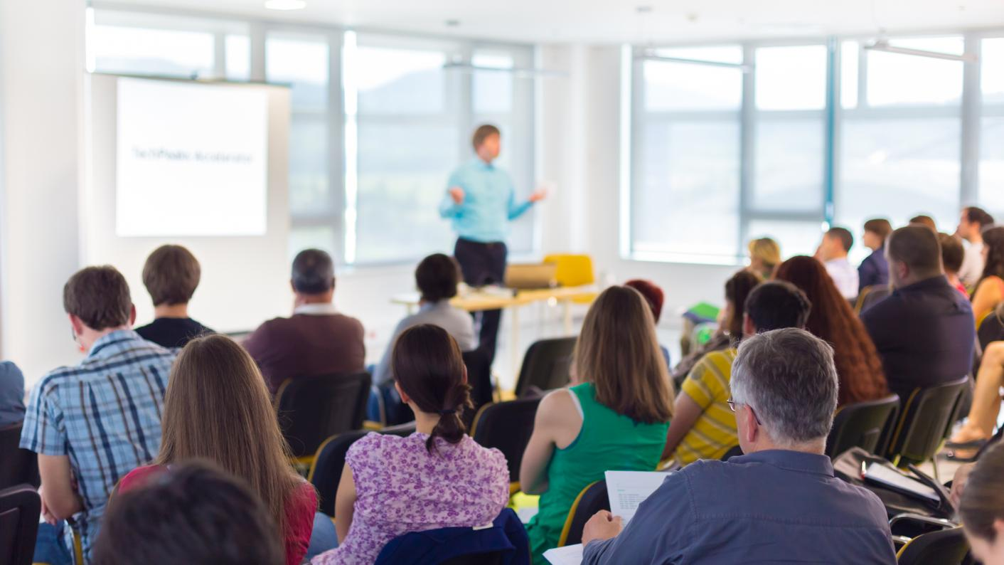 Teachers listening to a speaker in a busy room