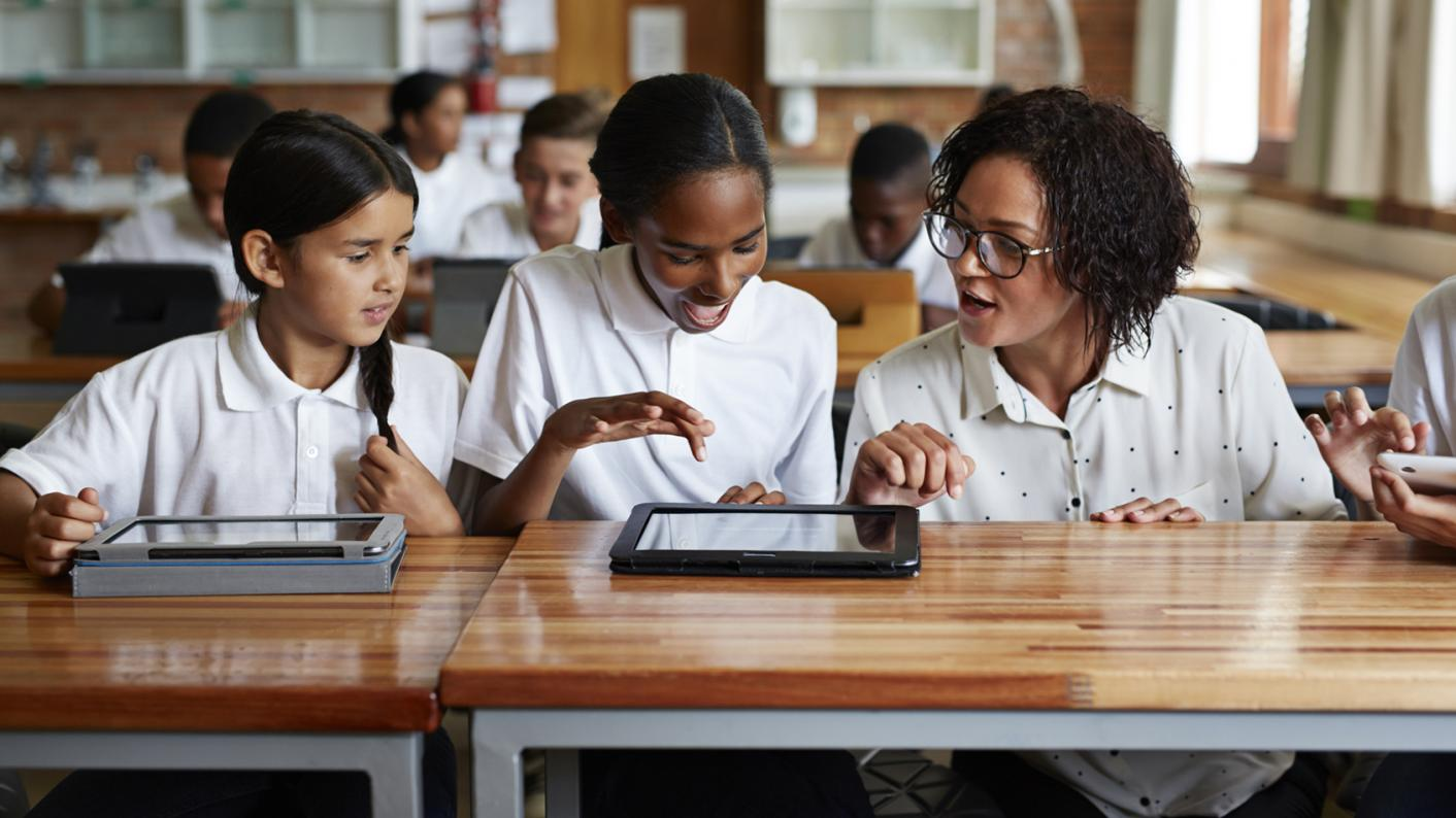 Children looking at content on a tablet in the classroom
