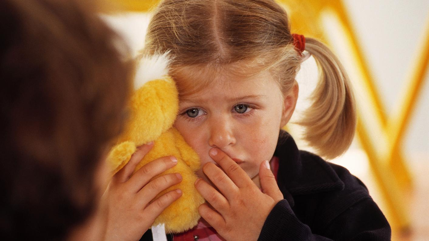 Young child crying and holding a soft toy