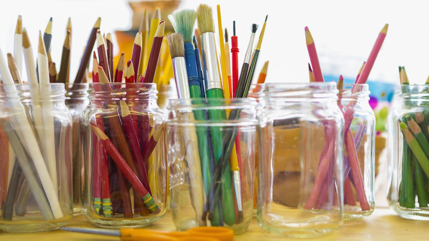 Different colours of pencils and pens in separate pots
