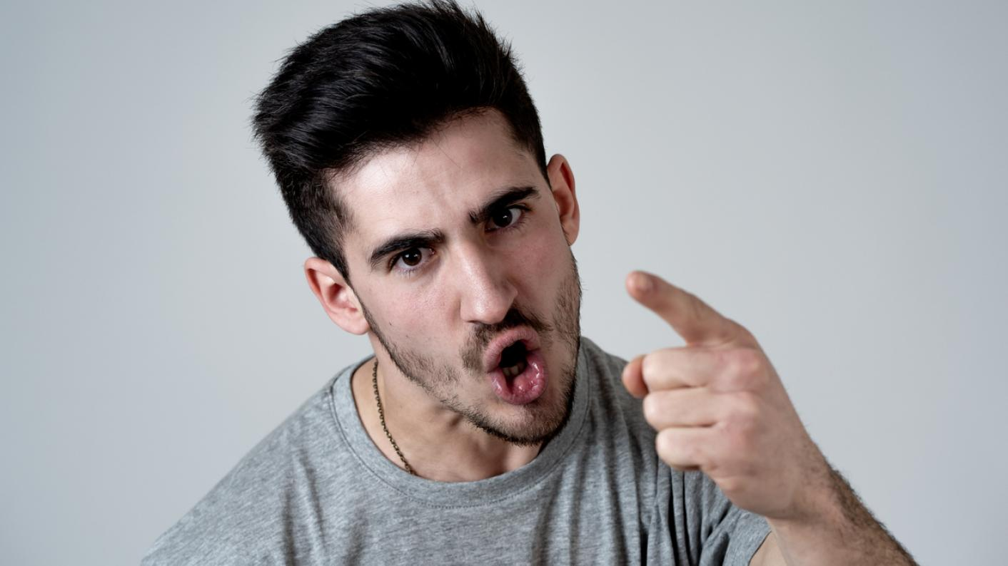Young man shouting and pointing his finger