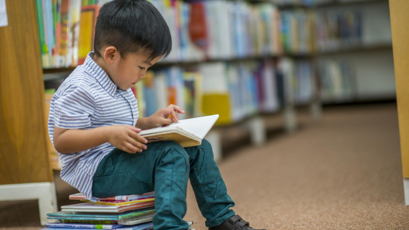 Small boy, sitting on a pile of books and reading