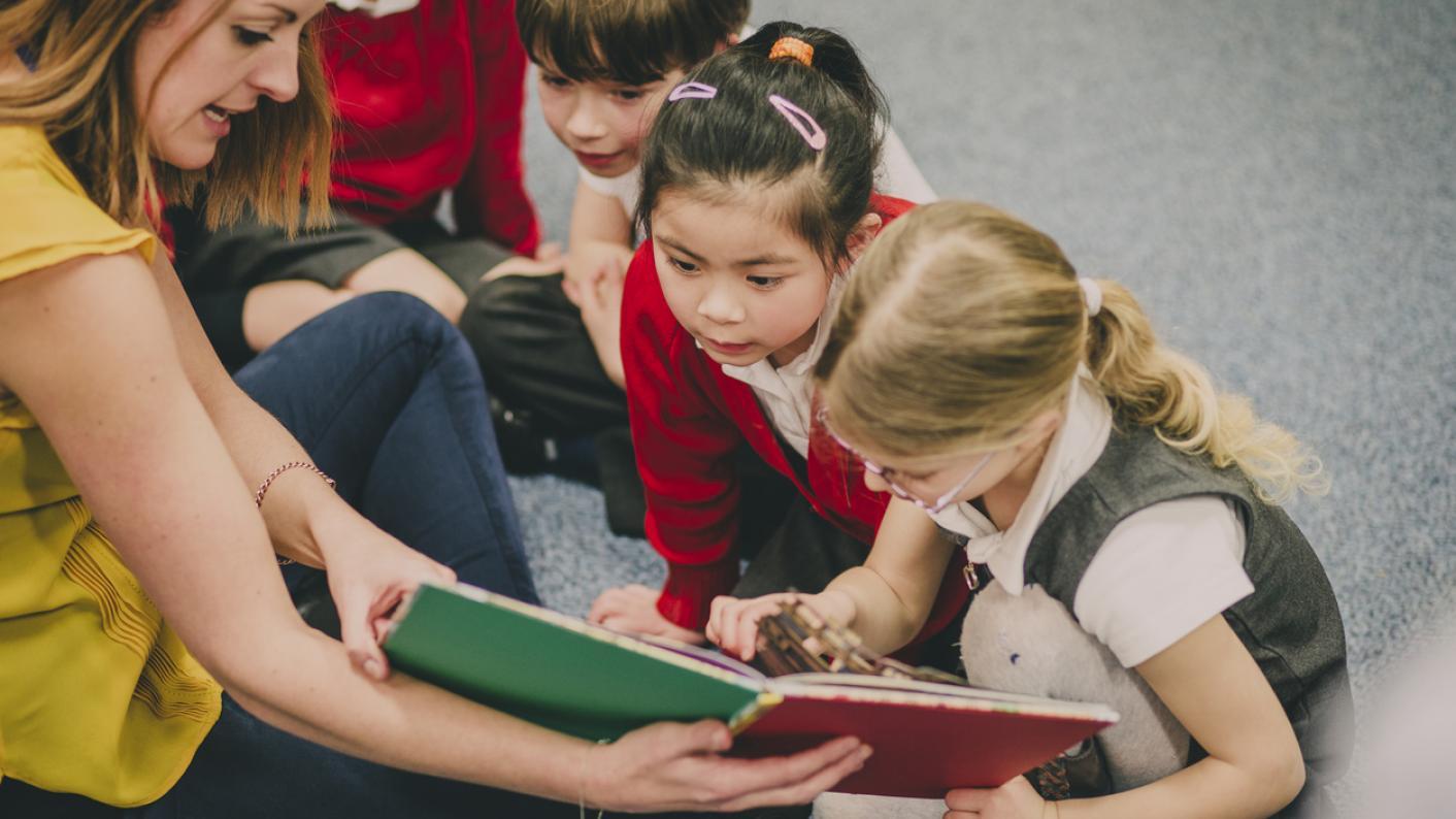 Children gathered around a teacher with a book
