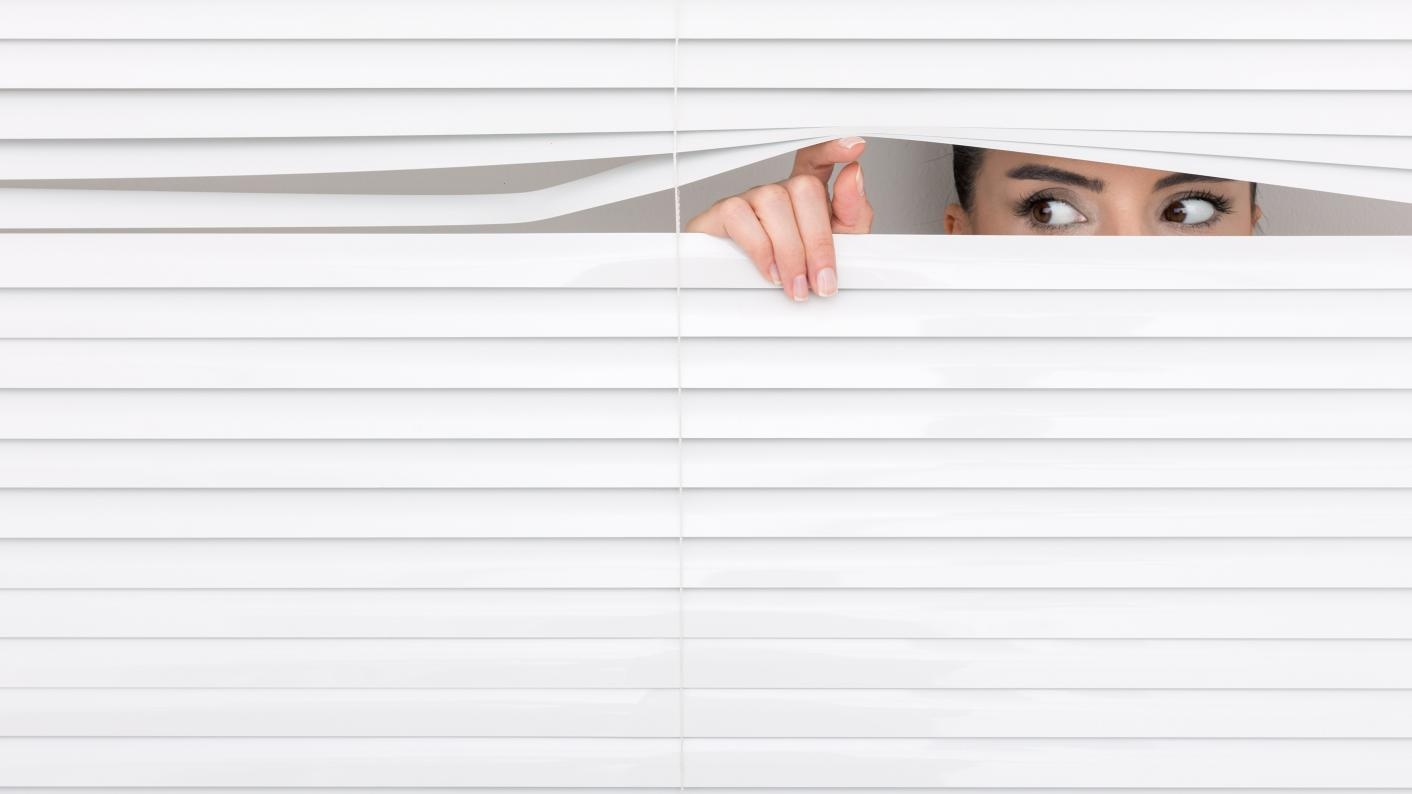 Woman peering out from behind blinds