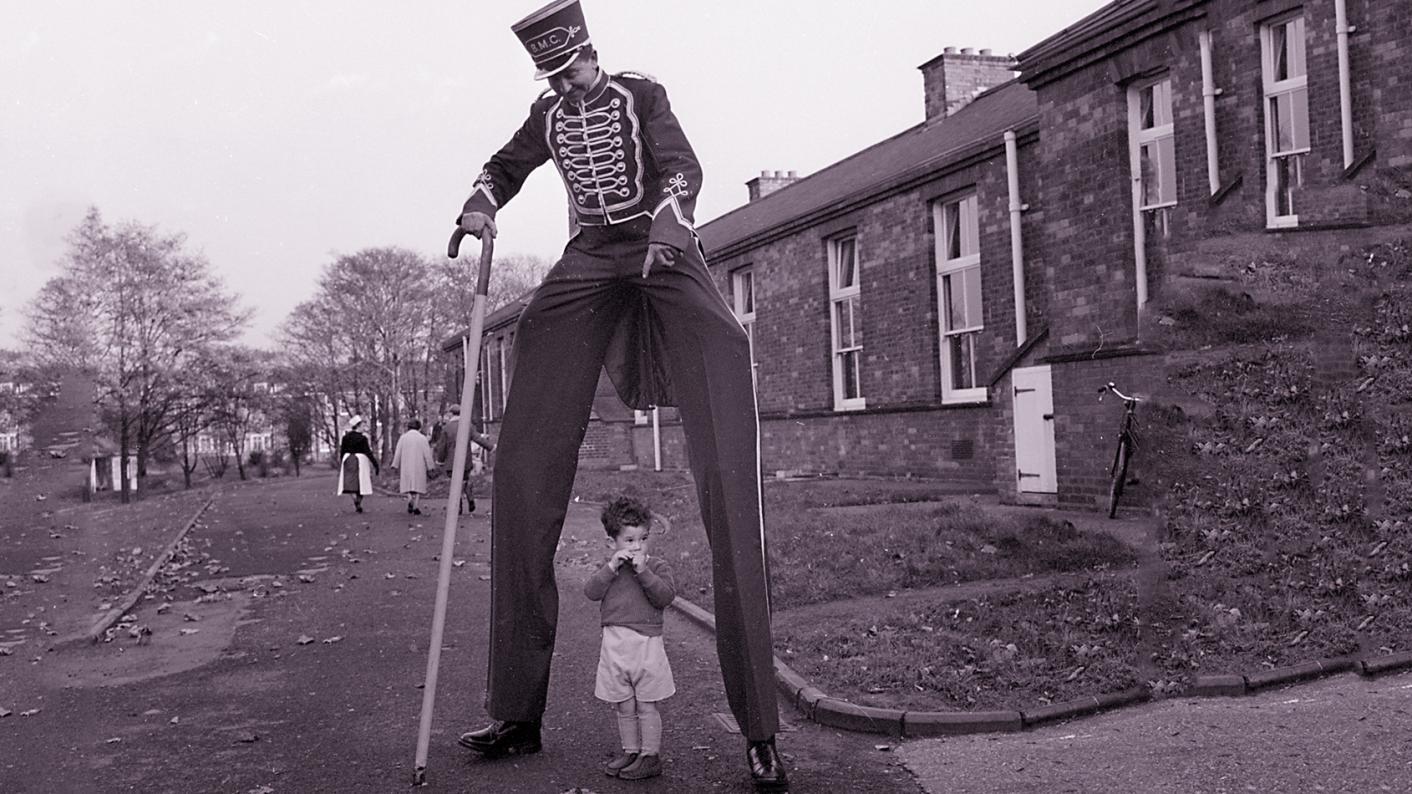 Man wearing stilts with child between legs