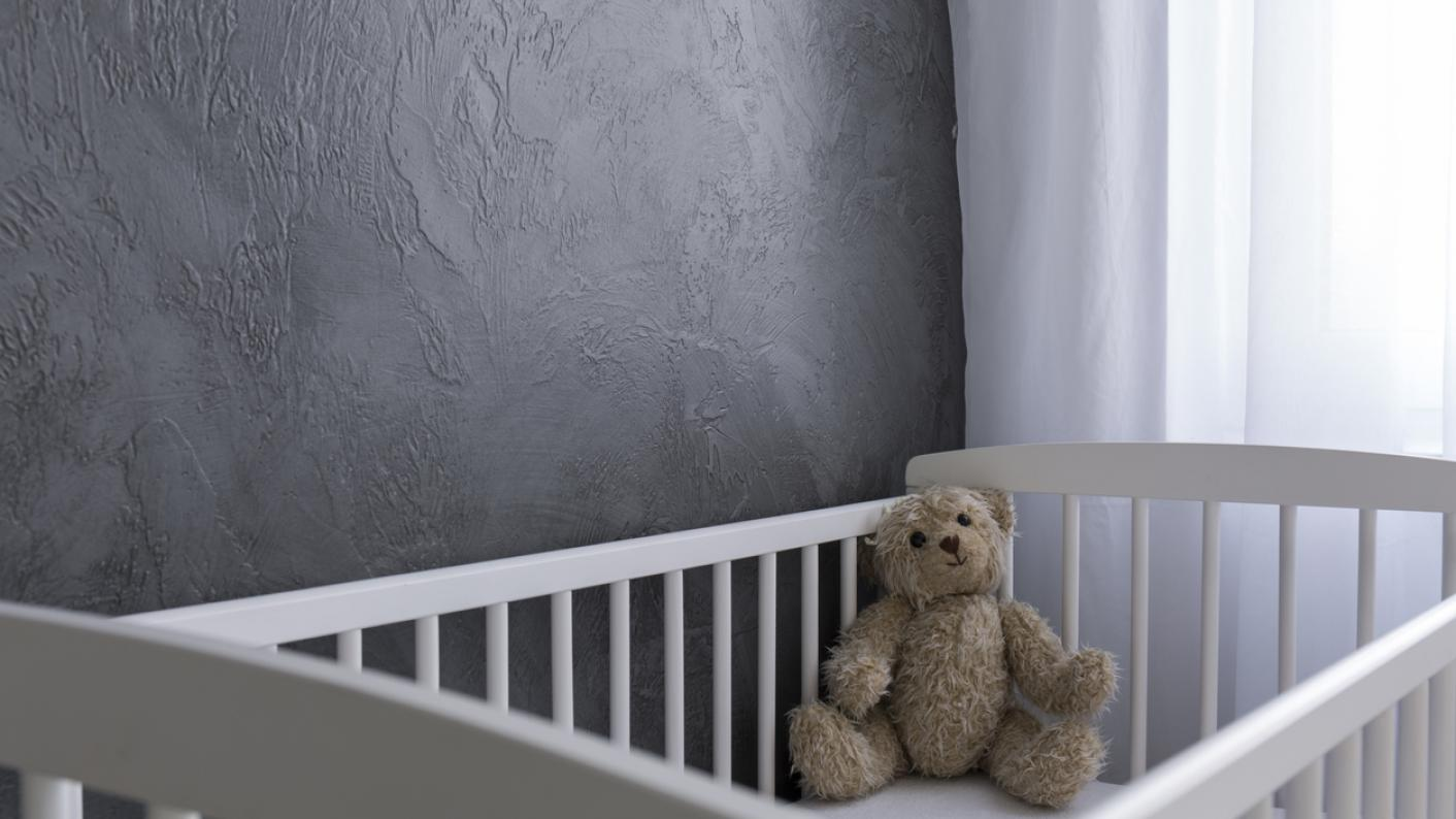 Empty cot, with teddy bear in corner