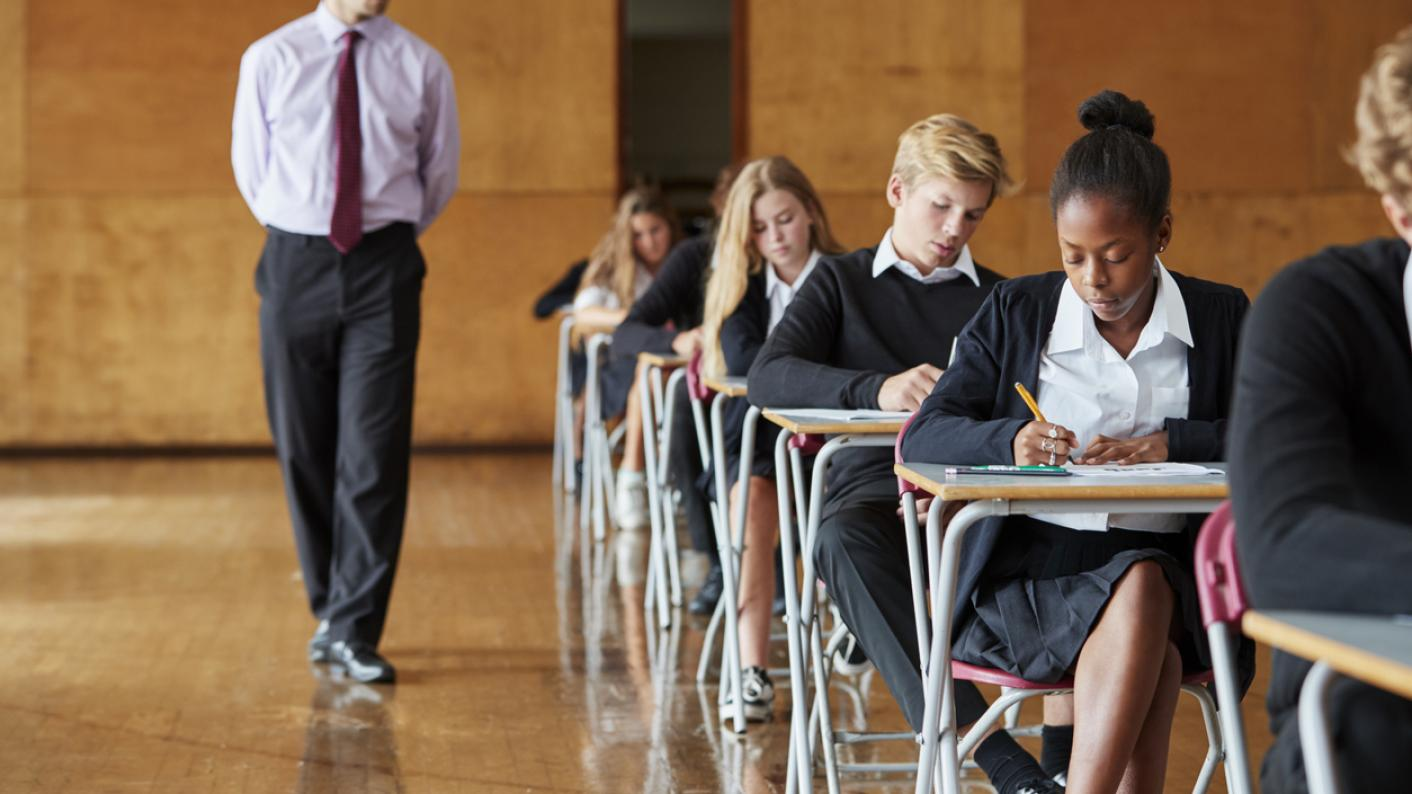 Pupils take exam, while invigilator paces between desks