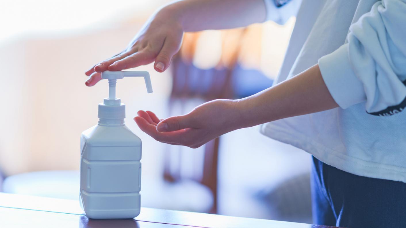 Child dispenses hand sanitiser from bottle