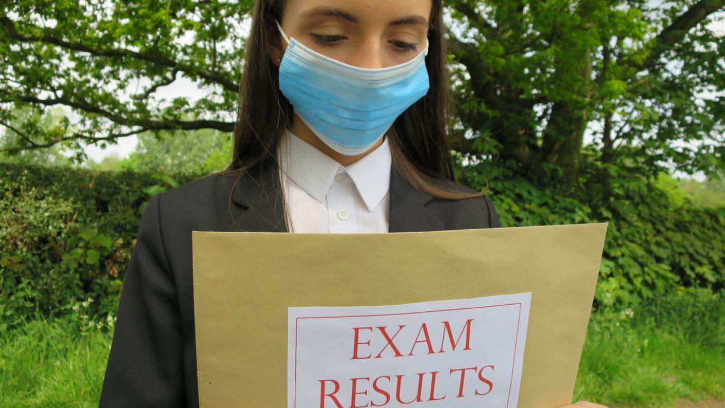 """Girl in face mask holds envelope labelled """"exam results"""""""