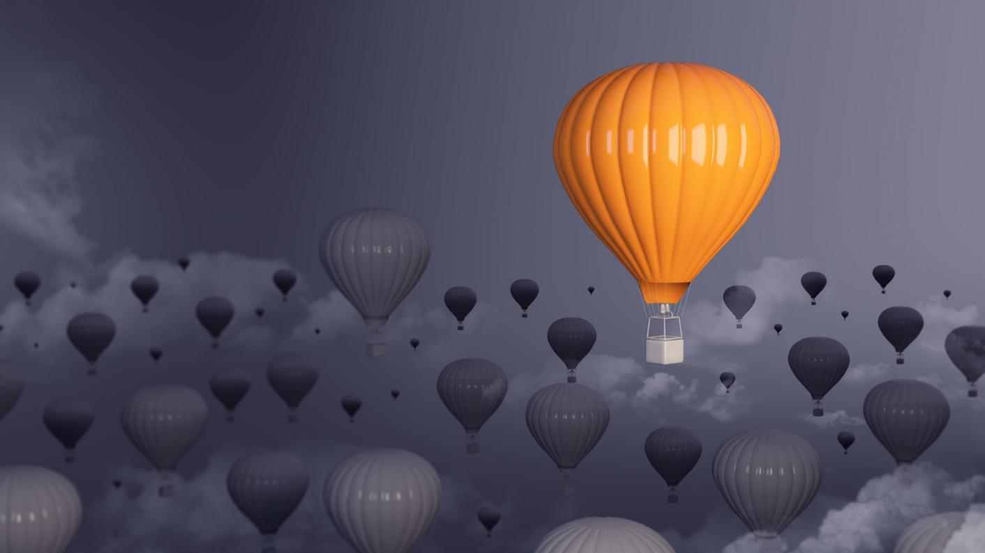 Yellow hot-air balloon, rising above mass of grey balloons