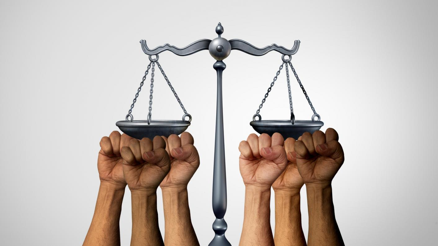 Several multiracial fists prop up the scales of justice