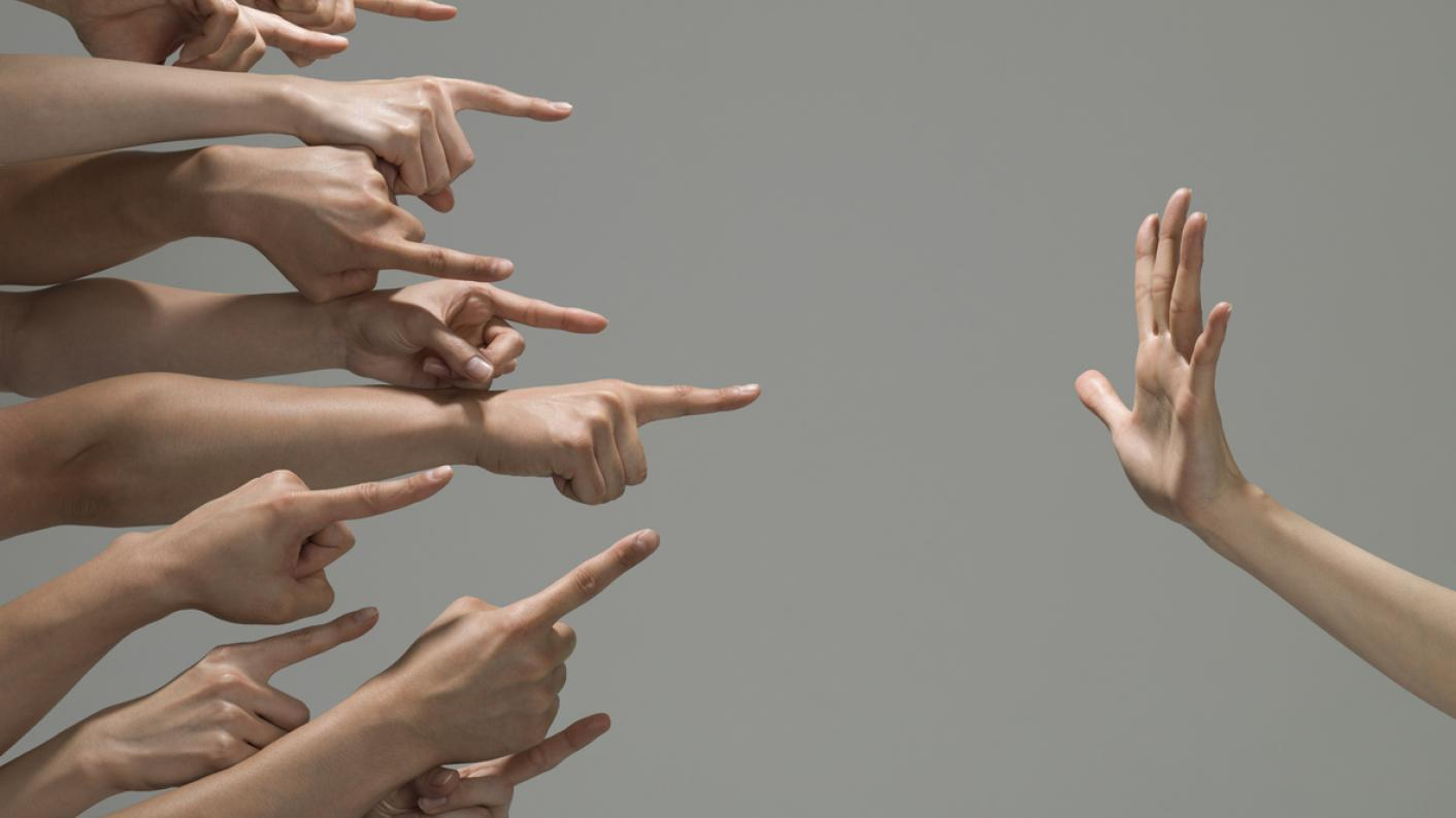 Several fingers, pointing in blame at one hand, which is held up to signify 'stop'