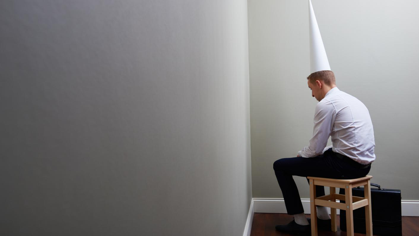 Man in suit, sitting in the corner, wearing a dunce's cap