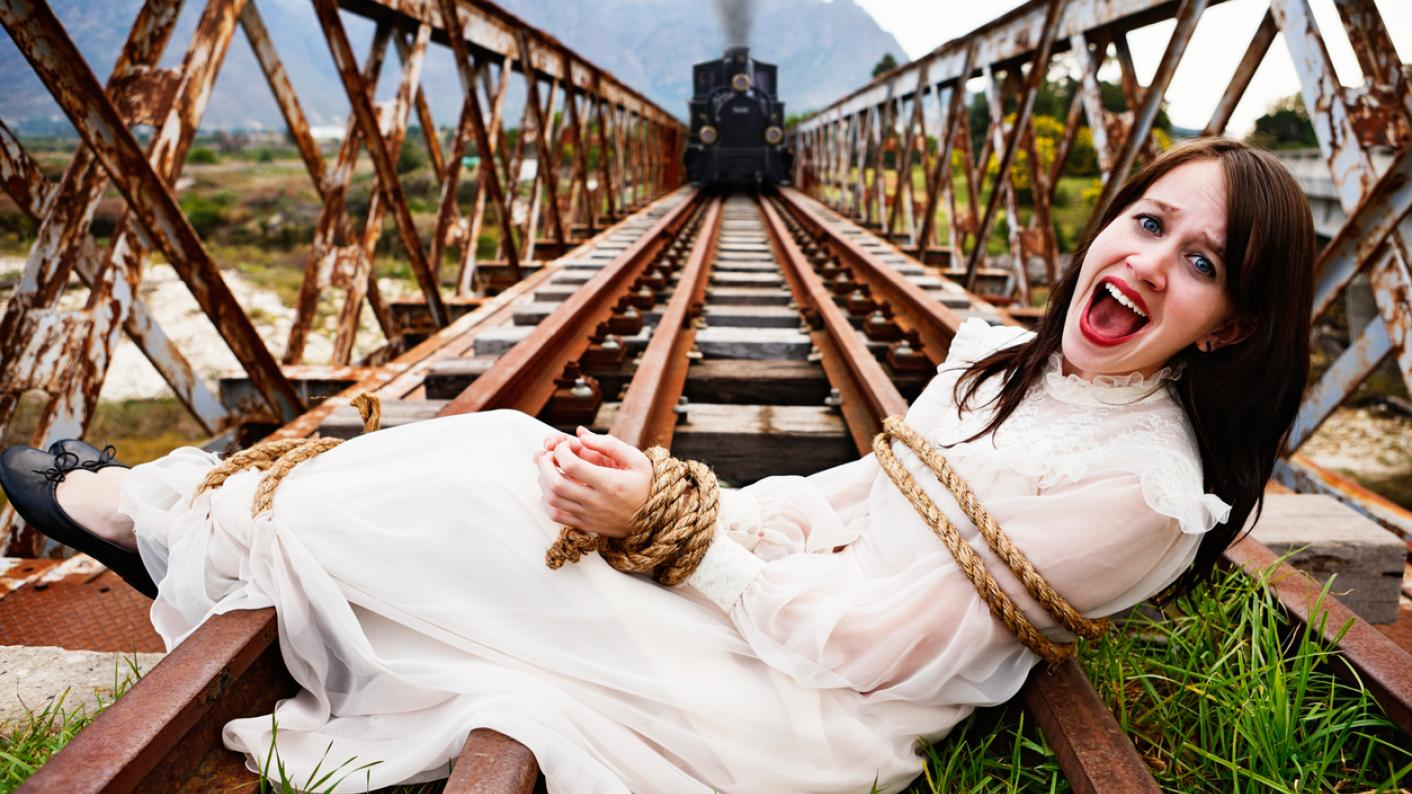 Woman tied to rail tracks, while steam train approaches in the distance