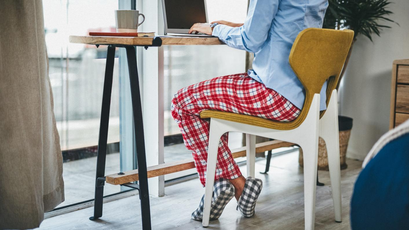 Woman, working from home wearing pyjamas and slippers