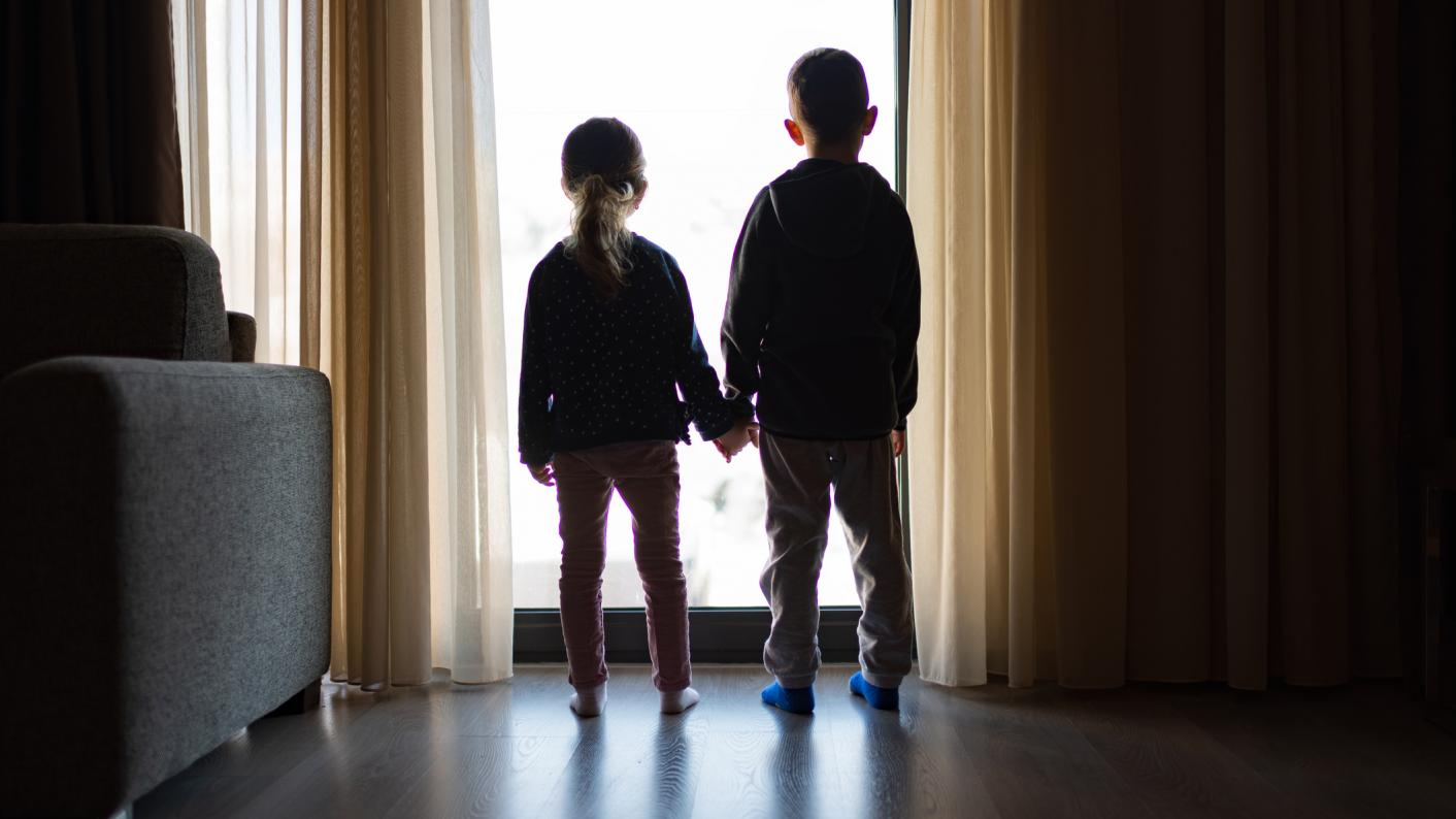Two small children, standing by a window