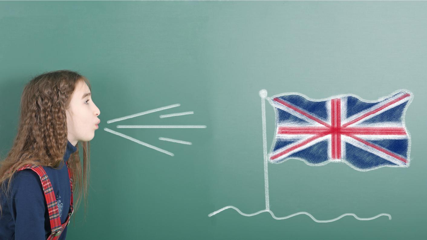 Schoolgirl next to blackboard blows on chalk-drawn image of Union Jack