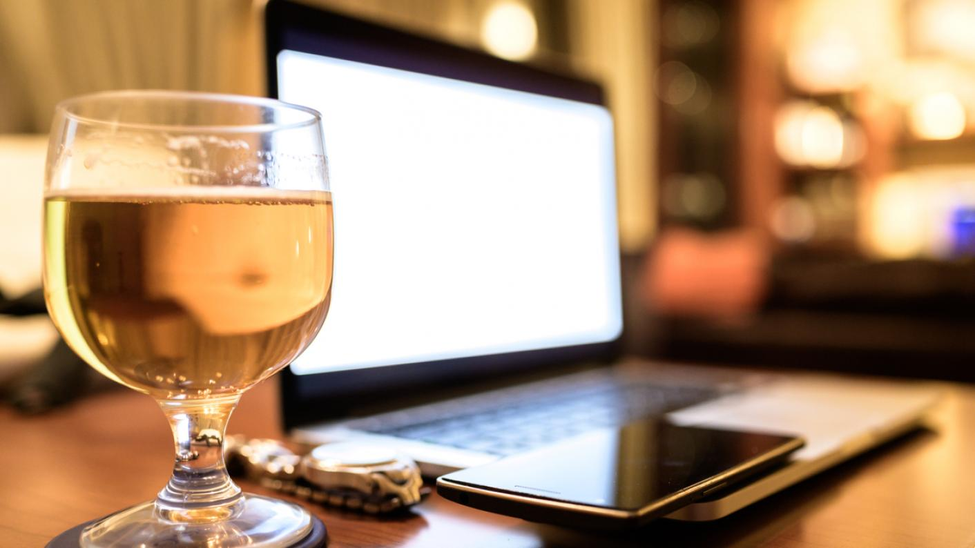 Glass of beer, next to laptop on table at home
