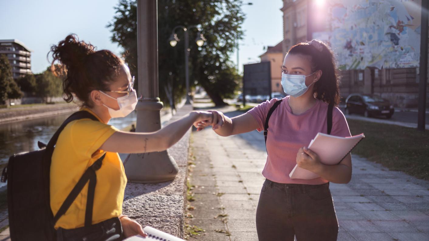 Two girls fist bump pandemic