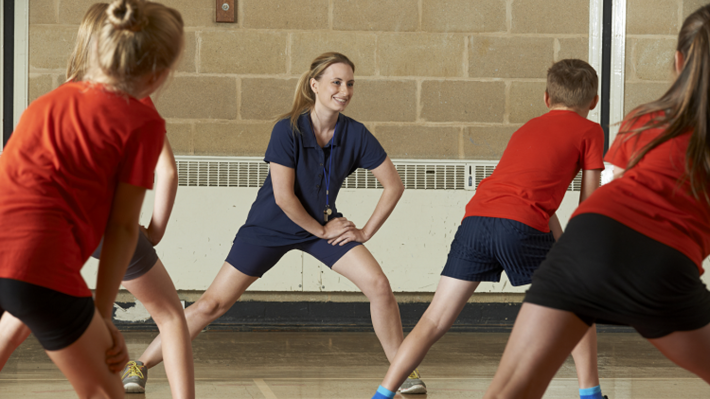 Secondary School PE Students Stretching & Performing A Warm-up Before Their Lesson