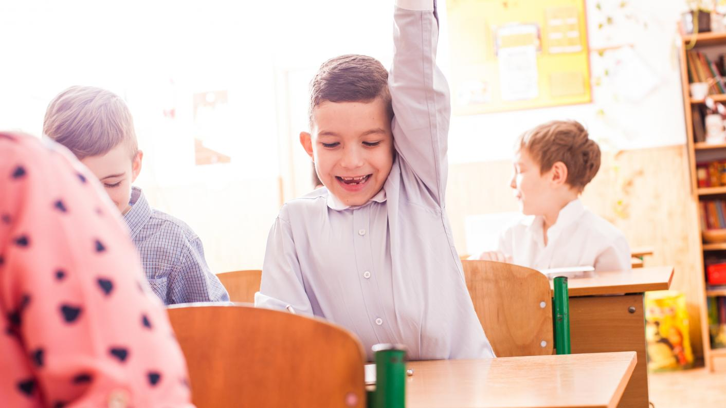 Boy Raising Hand To Answer A Question To A Fun Game In Primary Classroom