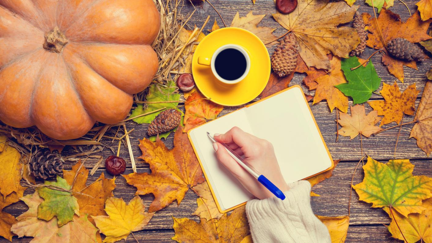 Autumn leaves on a table and a person writing autumn poetry