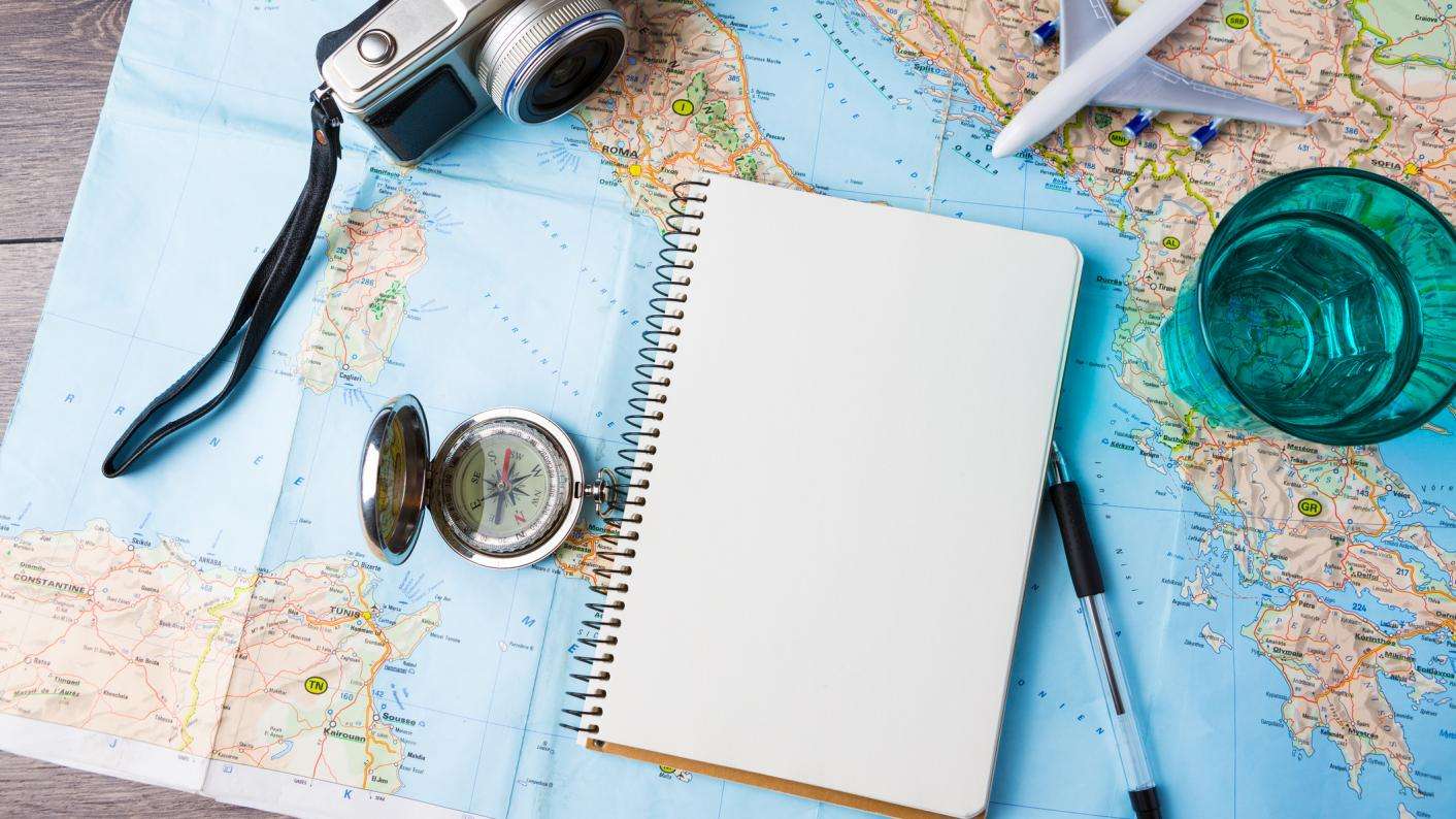 Map on a table with a notebook, pen and camera, improving map skills