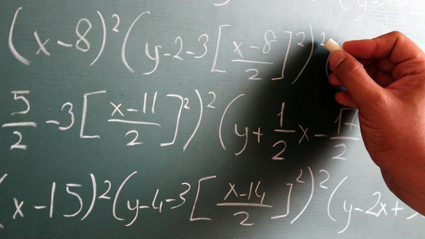 Teacher Writing Algebra & Maths Symbols On Blackboard To Test Students