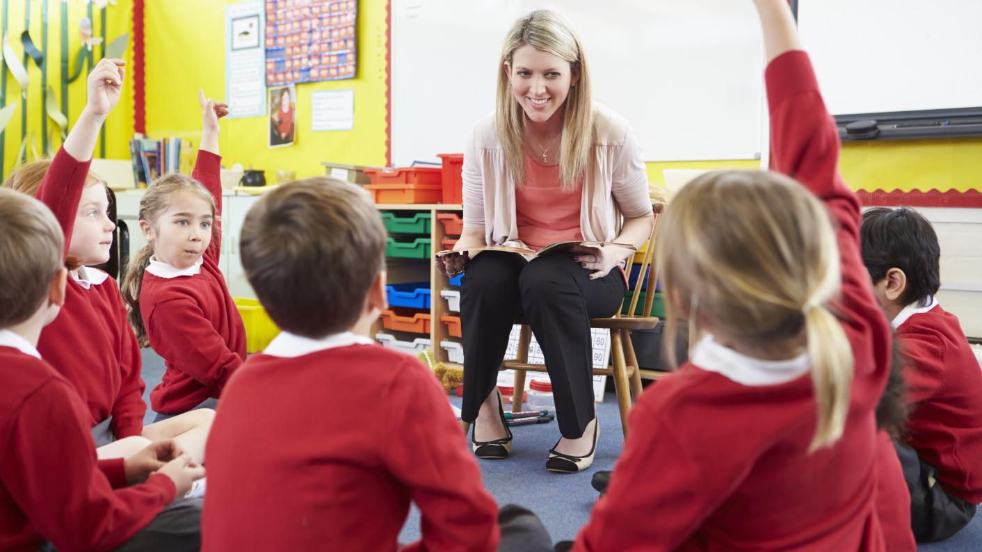 Teacher Surrounded By Engaged Pupils With Reading Activities