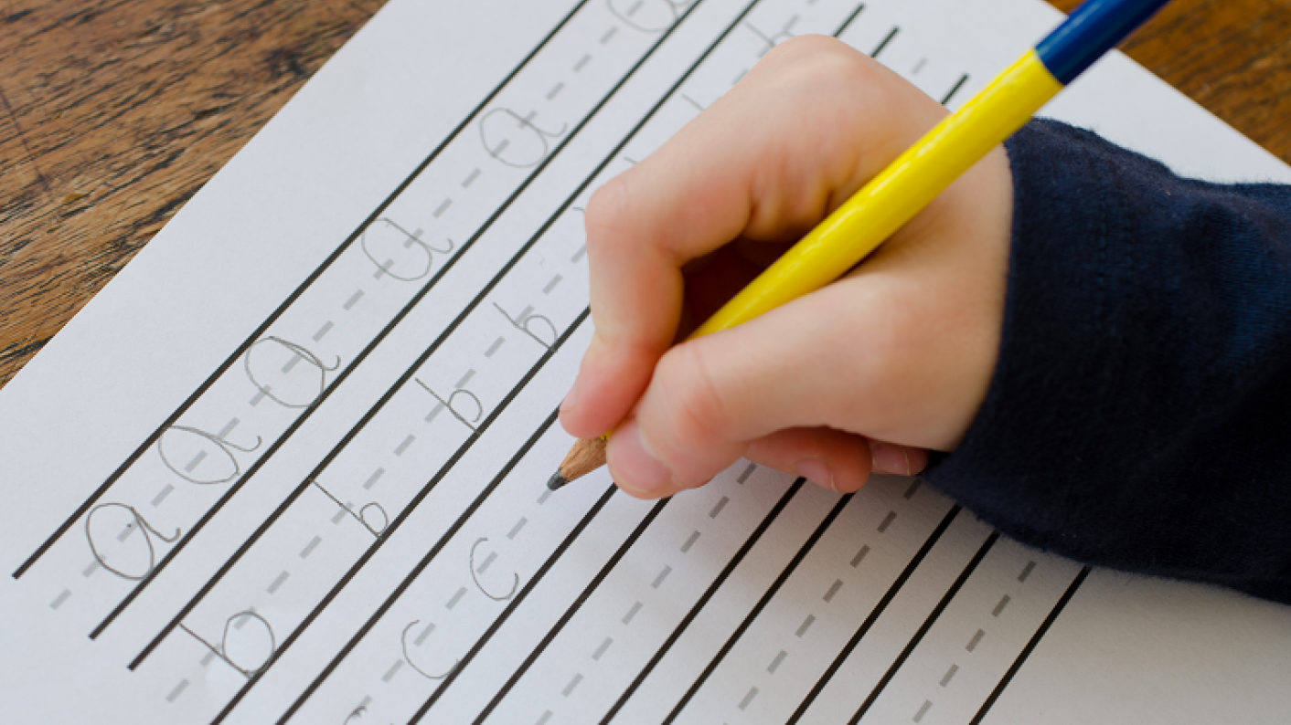 Pupil using a handwriting resource line guide to practice hand writing skills